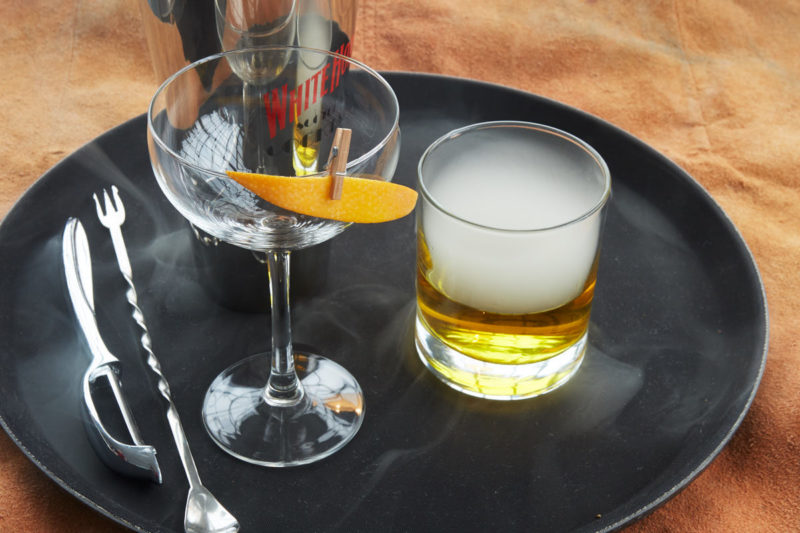 Cocktailglas, værktøj og en cocktail med røg