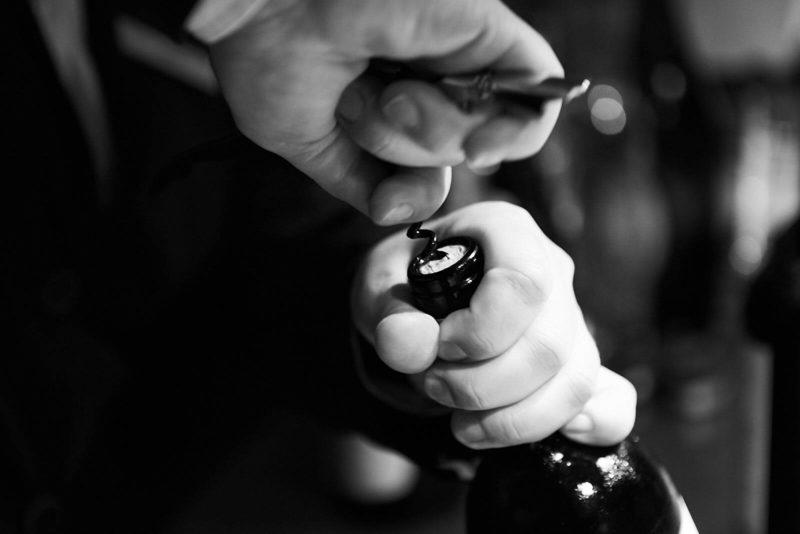 Tjener åbner en skøn flaske vin
