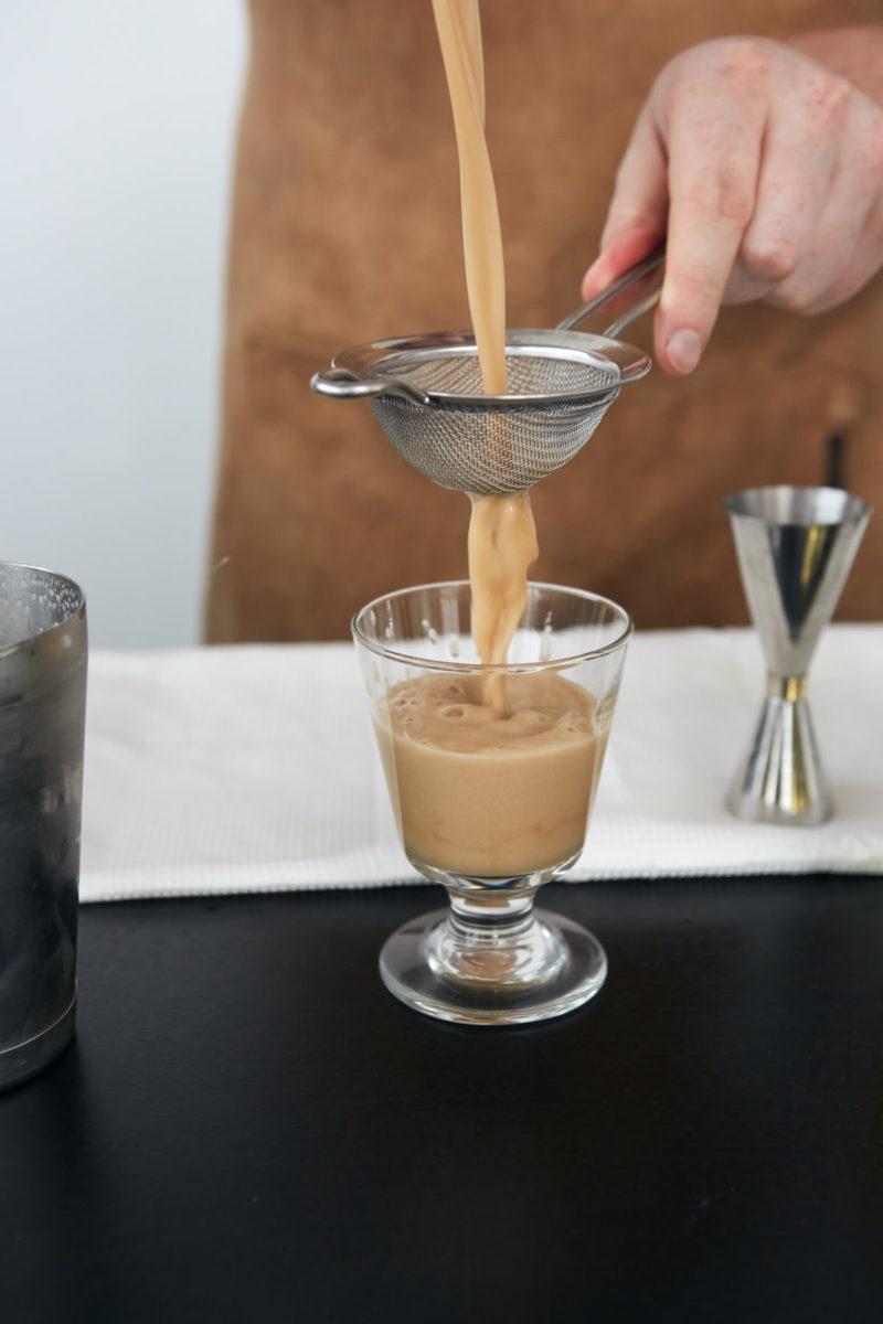 Bartender hælder espresso martini op i afkølet glas